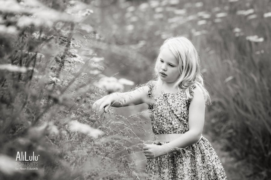 young girl picking flowers in fields