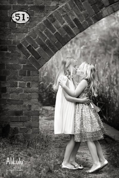 sisters kissing near bridge