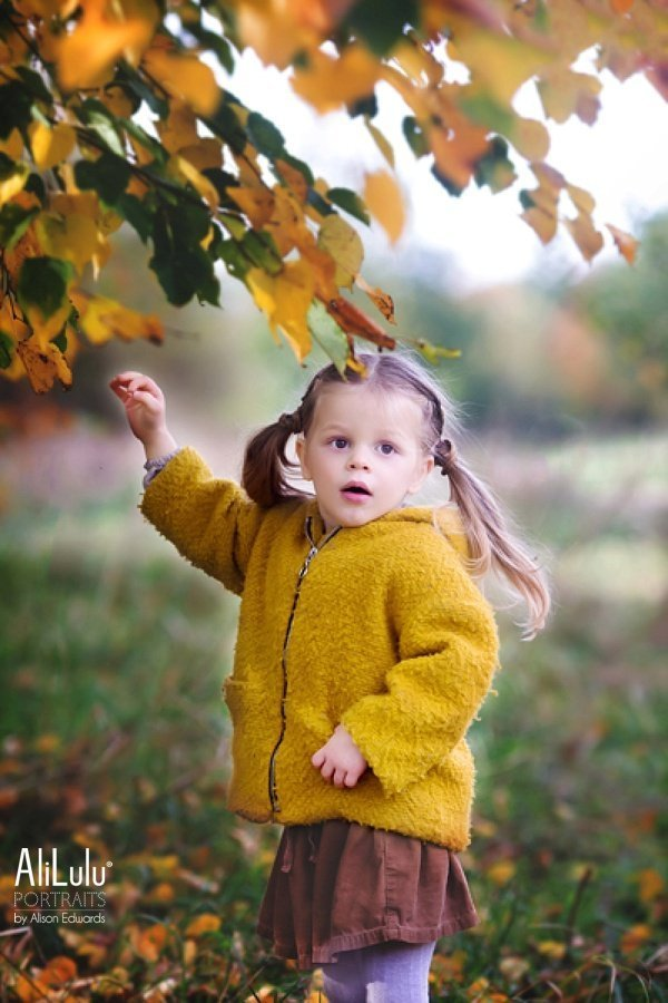 girl picking leaves from autumn trees