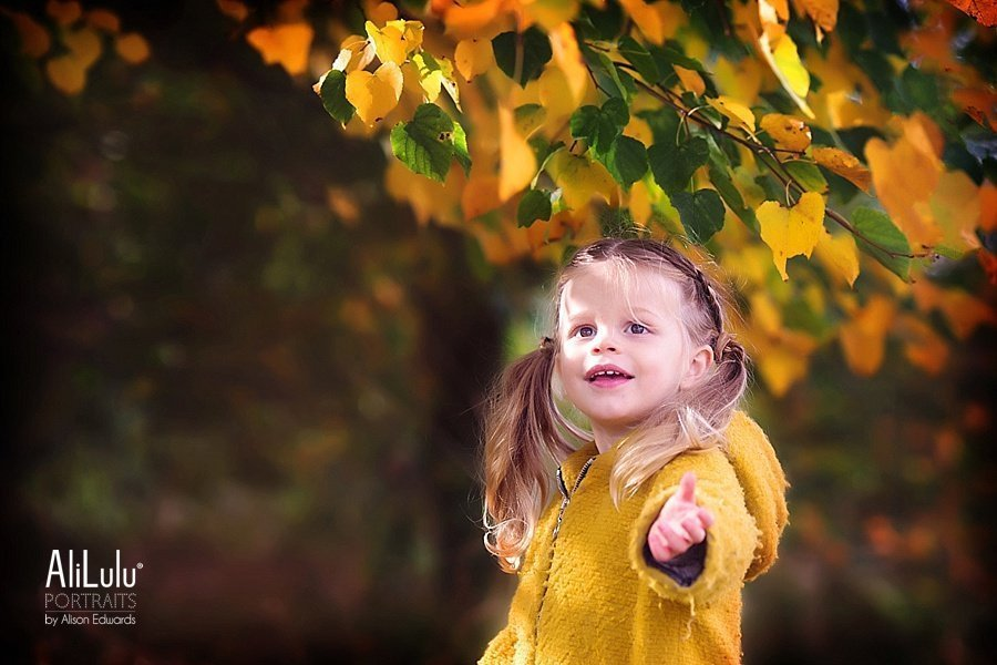 girl smiling under autumn leaves