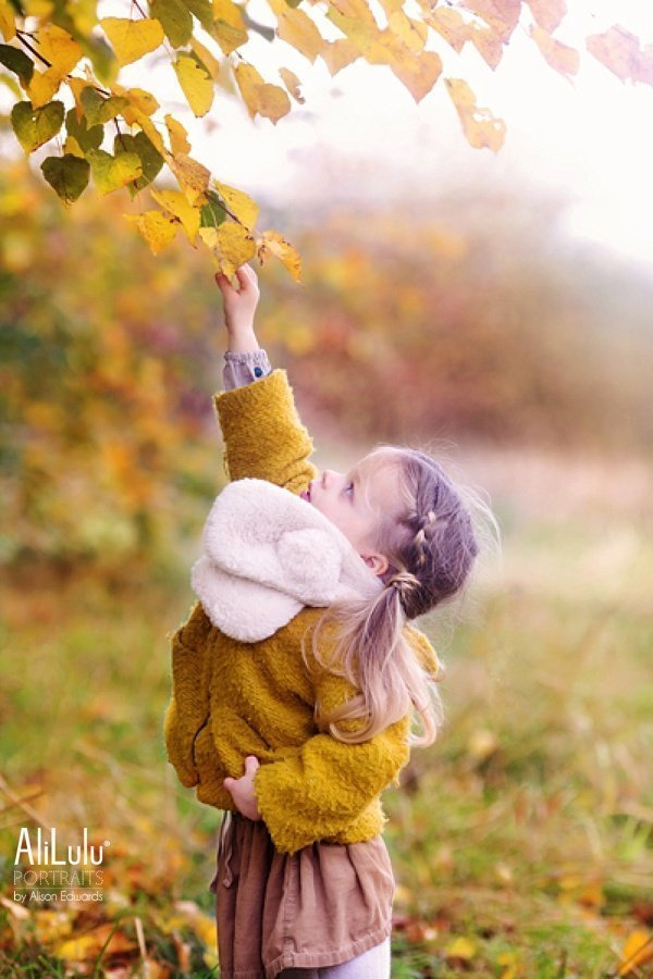 girl picking leaves on autumn photo shoot