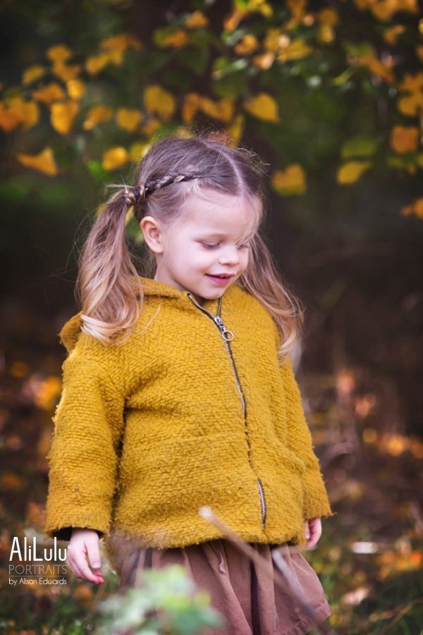 girl smiling in yellow coat autumn time