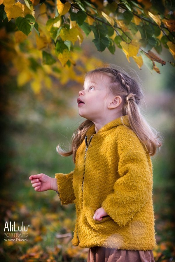 girl looking up under tree in autumn