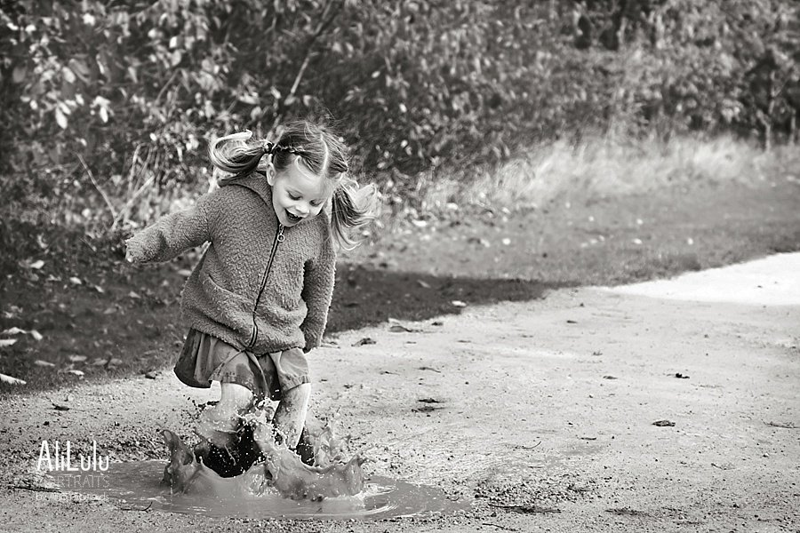 girl splashing in big puddle laughing