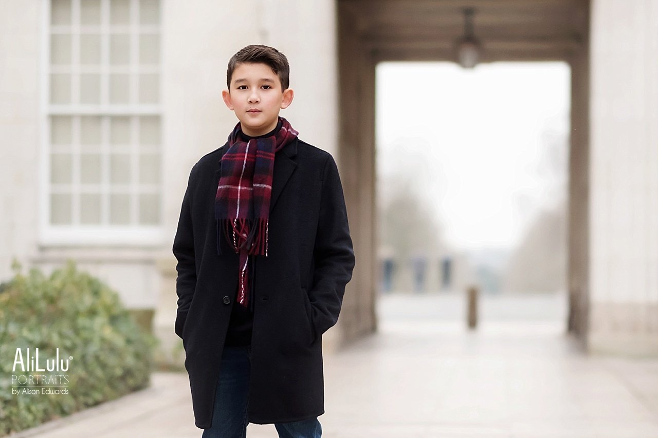 boy wearing black coat and burgundy check scarf