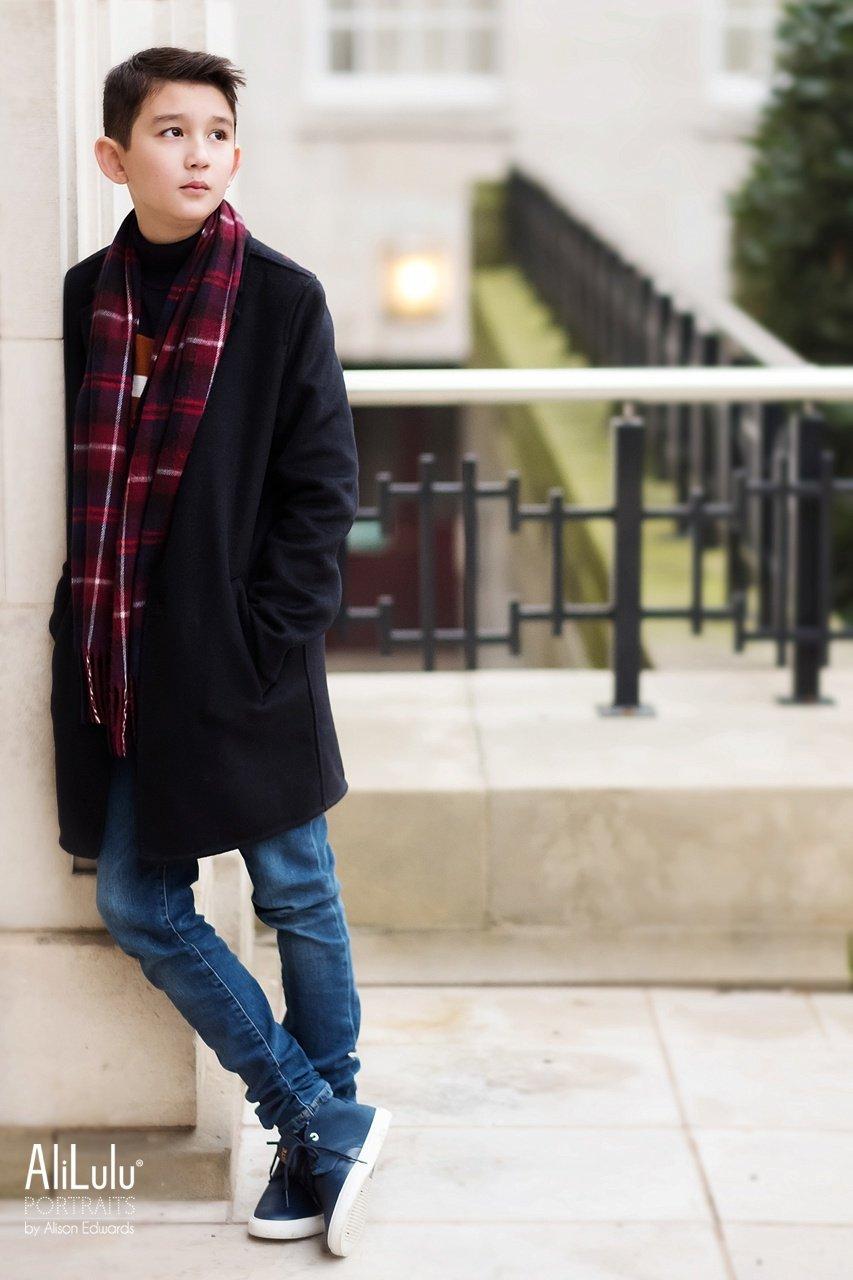boy leaning on wall side profile wearing lacoste pumps