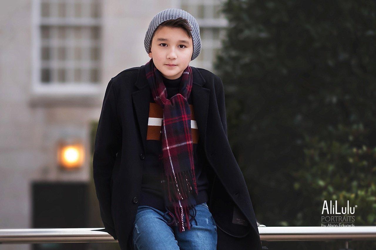 boy wearing lacoste beanie hat sitting on rail