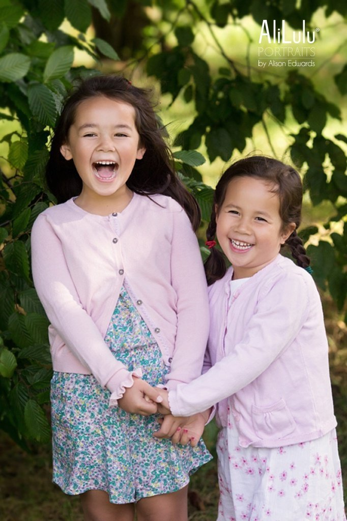 sisters laughing holding hands
