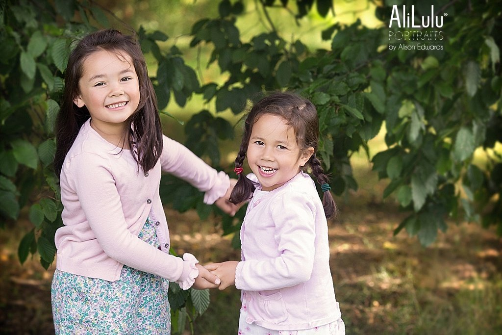 sisters holding hands playing in park