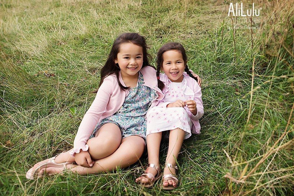 girls sitting in grass in park