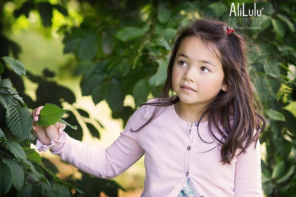 young girl looking sideways near trees in park