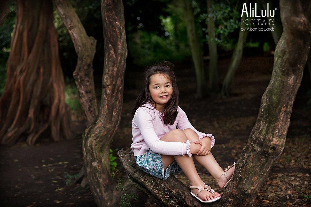 girl sitting in tree trunks in park