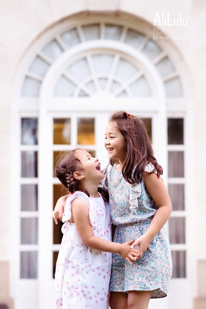 girls laughing in front of arch window