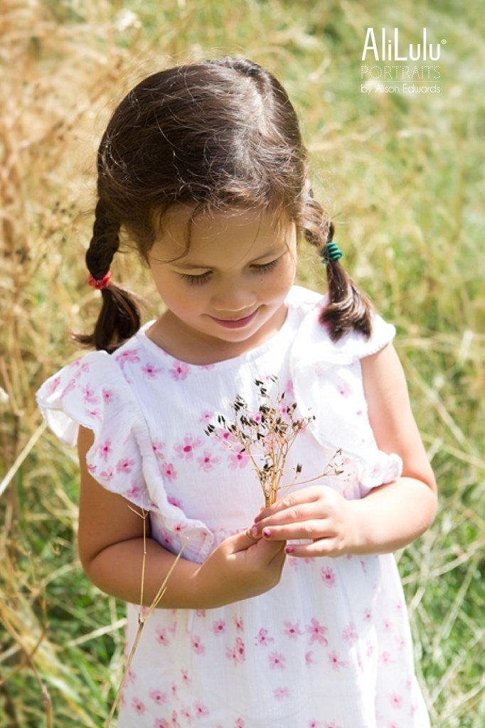 young girl looking at flowers in park