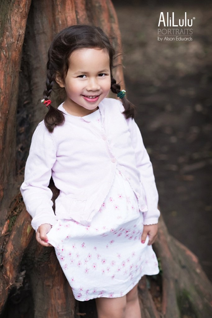 girl leaning against tree in park