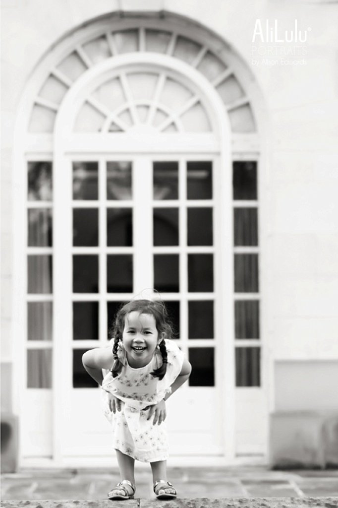girl laughing in front of arch window