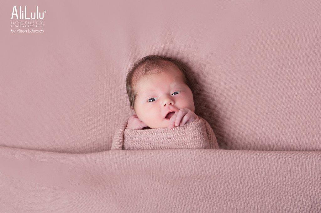 baby girl on pink blanket eyes open