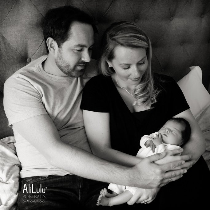 mum and dad holding and looking at baby girl