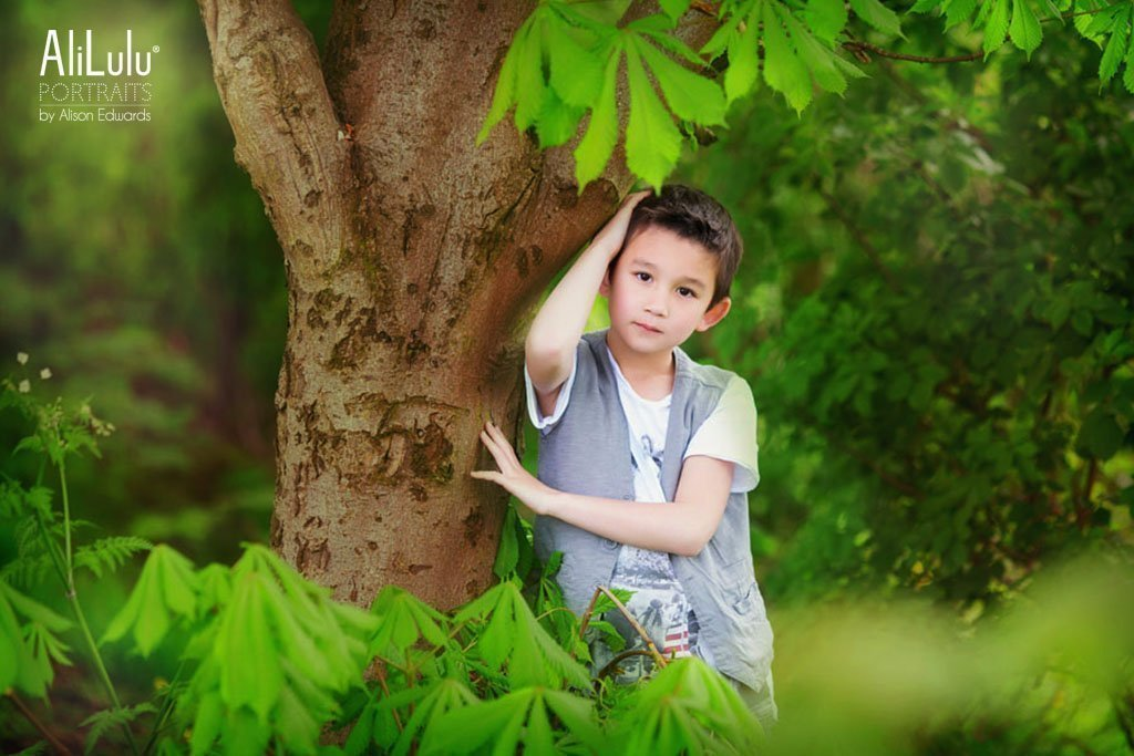 Mini photo sessions with Young boy leaning against tree in park