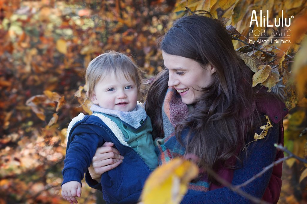mum and son in autumn leaves