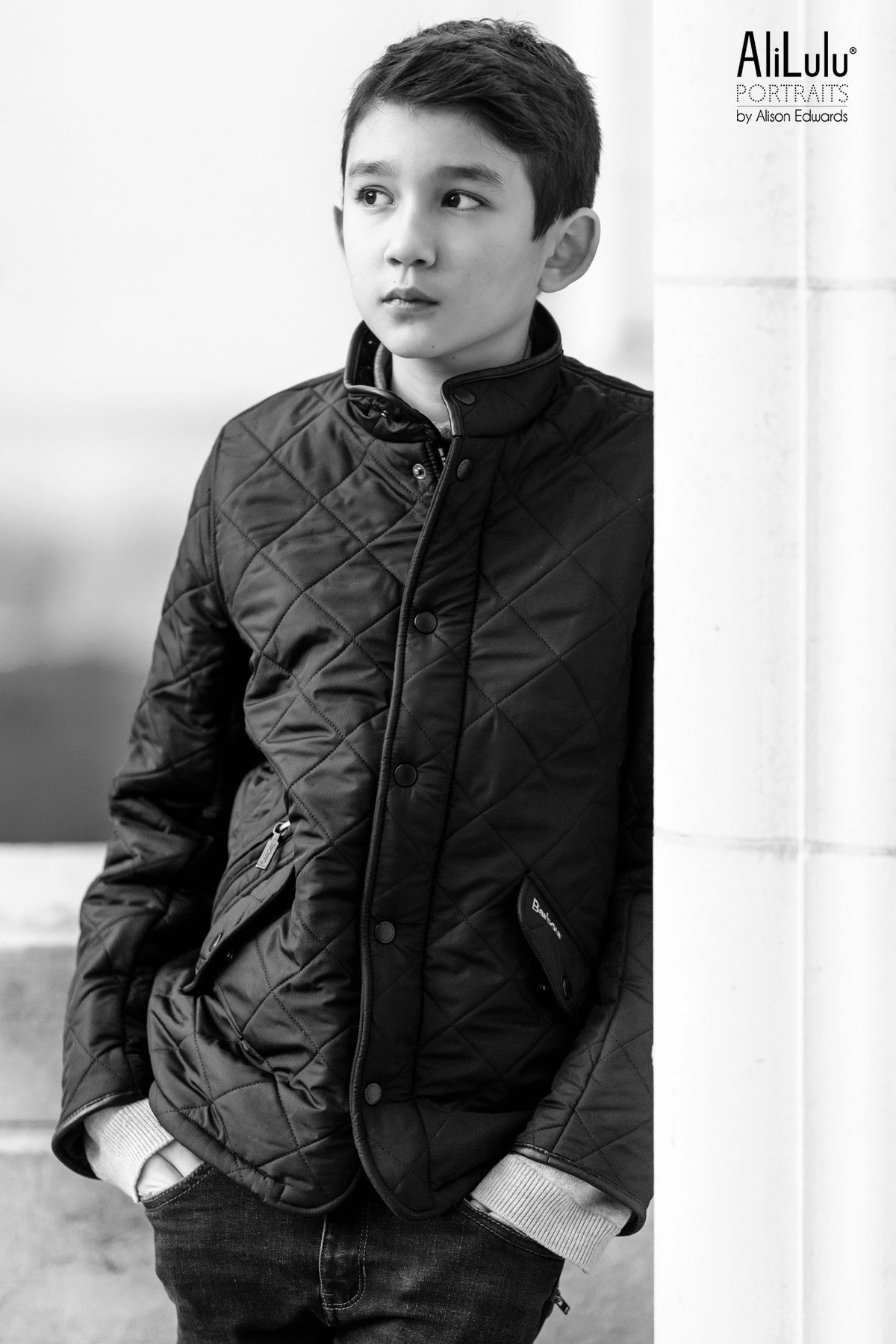 boy in barbour coat leaning on wall