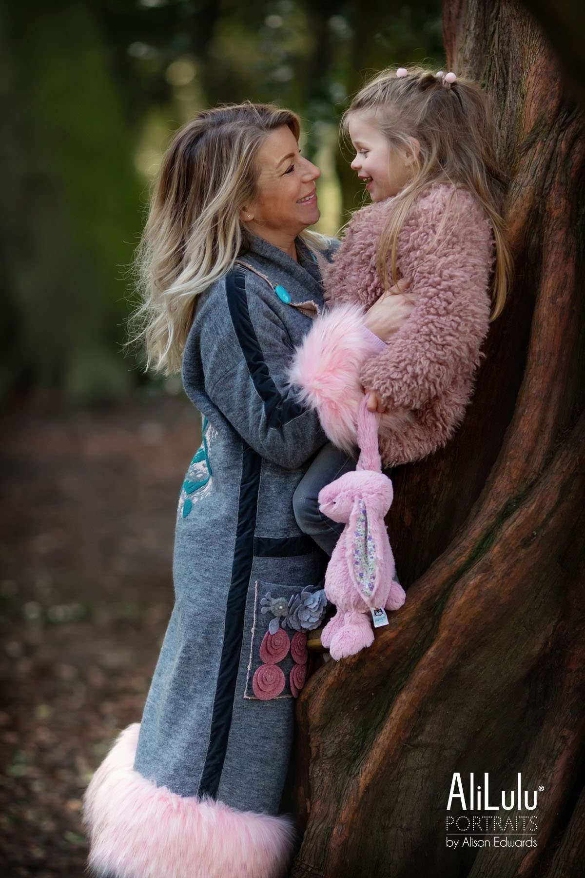 mummy and young daughter smiling in park