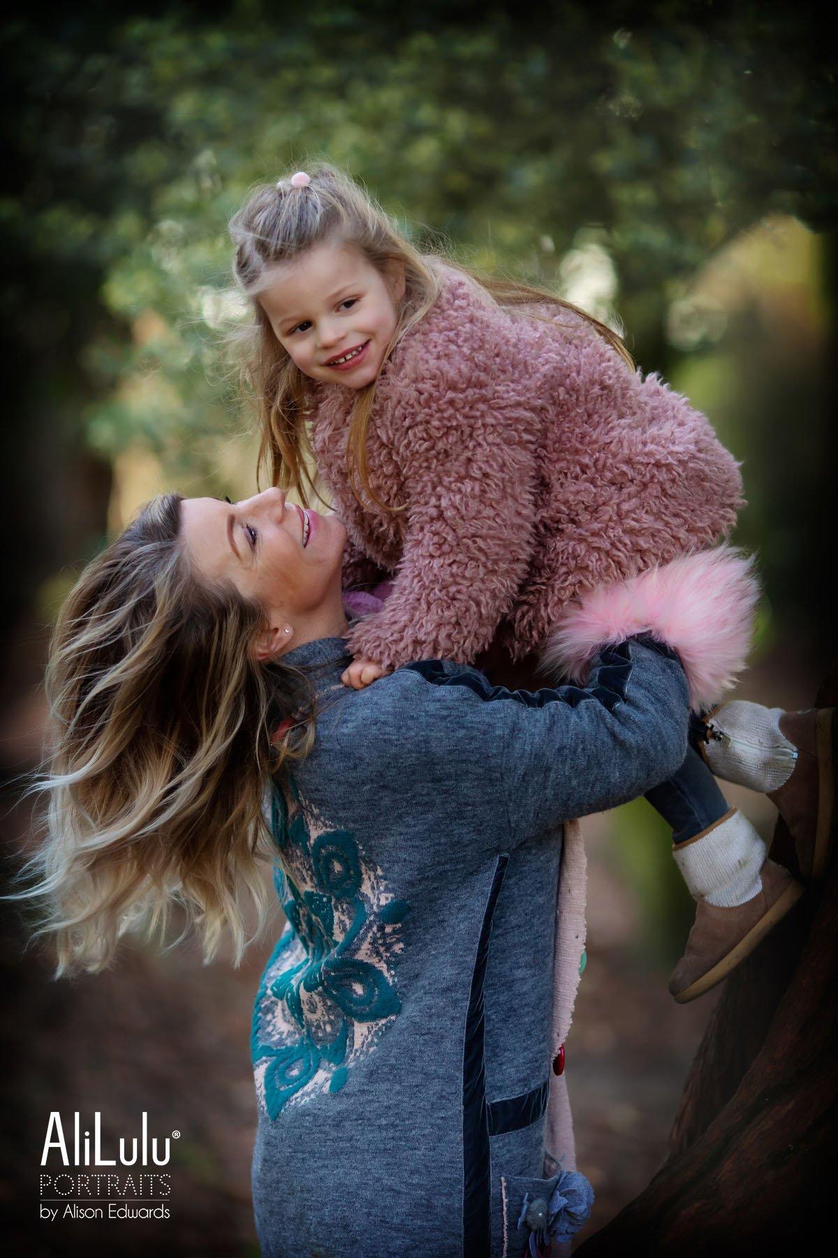 mum lifting daughter in air in park