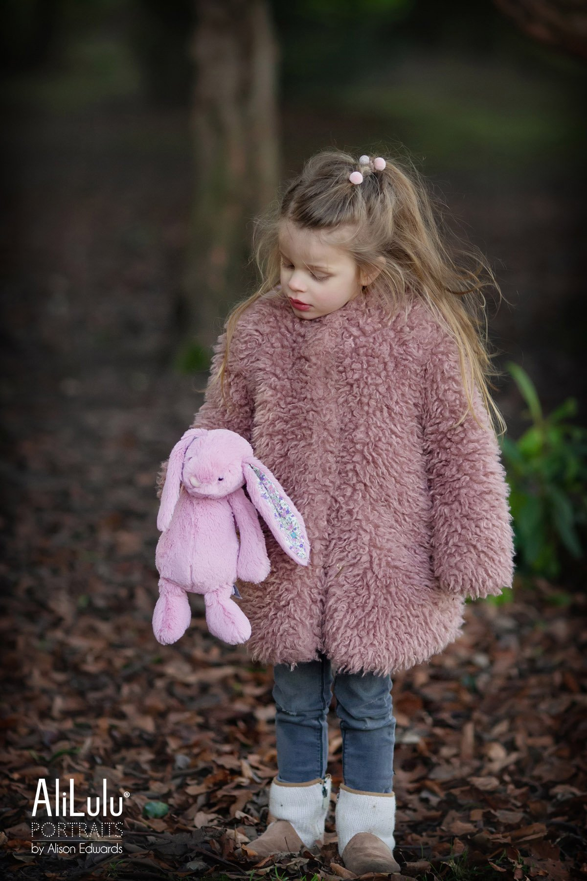 girl looking at her bunny bear in park