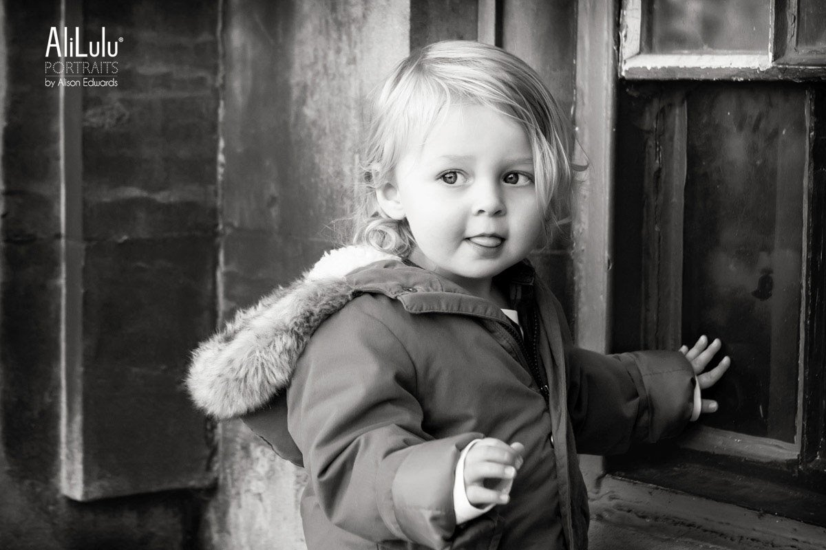black and white photo of cute boy in park