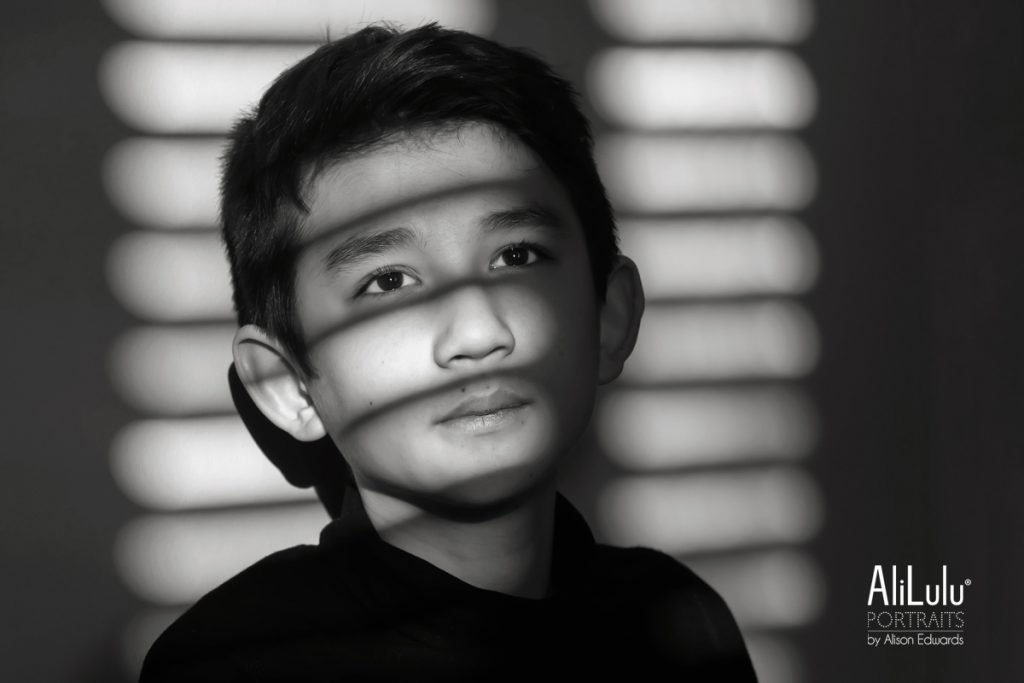 black and white portraits of boy's face in shadows